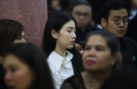 "A mourner cries to herself at the funeral of actor Bhumiphat ""Hem"" Nittayarot, who committed suicide earlier this week. The service is held at Wat Lat Pla Khao in northern Bangkok until September 29."