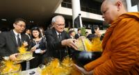 Chief charter writer Meechai Ruchupan leads hundreds of statesmen and civil servants in a Buddhist rite, offering alms to 89 Buddhist monks to make merit for the late |King Bhumibol Adulyadej.