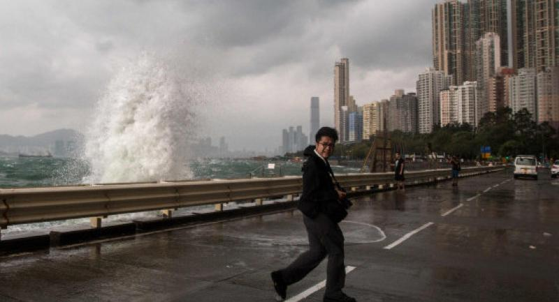 A pedestrian crosses a road next to a coastal barrier as Typhoon Haima approaches Hong Kong Friday, during a typhoon signal eight warning. AFP PHOTO / ANTHONY WALLACE