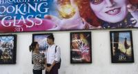 A couple standing next to movie posters at the Naypyidaw cinema in downtown Yangon. Photo/AFP