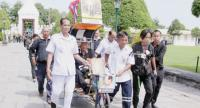 Officials and fellow mourners accompany disabled Pan Meunyot, 84, into the Grand Palace on his tricycle yesterday. Pan travelled from his hometown in Buri Ram to Bangkok to pay respects to the late King.
