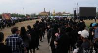 Mourners wait in lines to pay respects to His Majesty King Bhumibol Adulyadej in front of his portrait at the Grand Palace Monday.