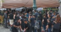 Police officers manning one of the nine checkpoints around Sanam Luang check a mourner