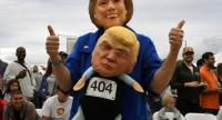 A woman wearing a Hillary Clinton mask carries a Republican presidential nominee Donald Trump doll during a Halloween parade in Long Beach, California on October 30, 2016. / AFP PHOTO / Mark RALSTON