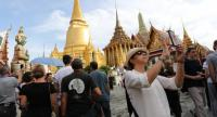 Tourists flock into the Temple of the Emerald Buddha inside the Grand Palace yesterday, as this was the first day they were allowed to visit the Temple since the distribution of tickets was suspended on October 14, after HM the King passed away. Visi