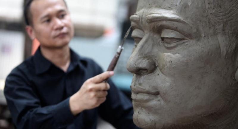 Pongpan Chantanmattha works on the clay model for a largescale bust of His Majesty that will be rendered in white marble. Hinon Co is donating the stone quarried in Saraburi.