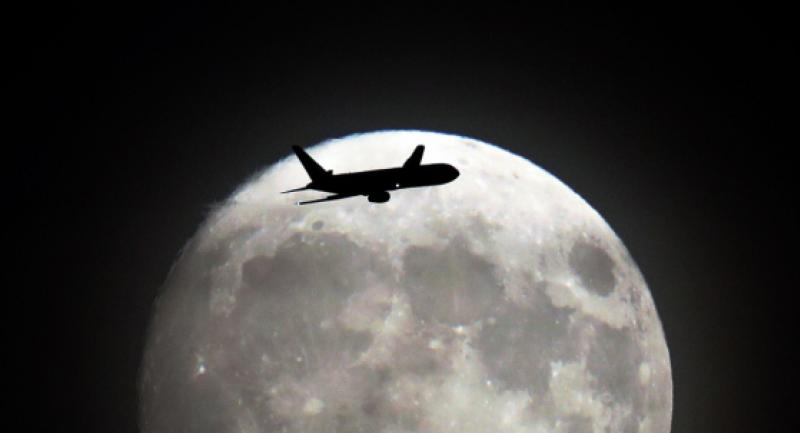 A commerical jet flies in front of the moon on its approach to Heathrow airport in west London on Sunday. Monday, the moon will orbit closer to the earth than at any time since 1948. / AFP PHOTO / Adrian DENNIS