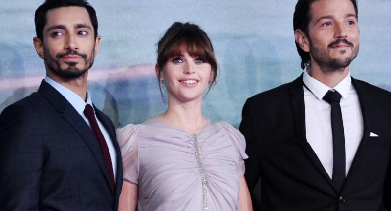 British actress Felicity Jones, centre, poses for photographs with British actor Riz Ahmed, left, and Mexican actor Diego Luna, right, during the premiere of