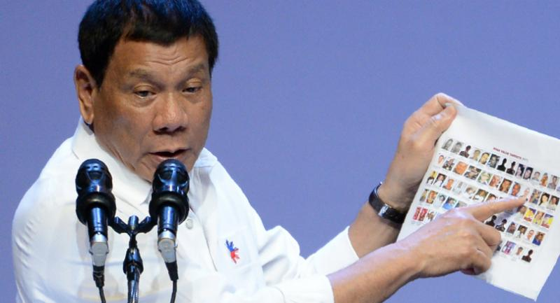 Philippines President Rodrigo Duterte shows images of alleged criminal Philippine politicians during his speech at a meeting with the Filipino community in Singapore on December 16, 2016. Duterte is on a two-day state visit. / AFP PHOTO