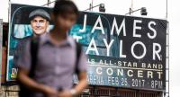 A man walks past a billboard promoting a planned concert by US singer James Taylor in Manila on December 21, 2016./ AFP PHOTO
