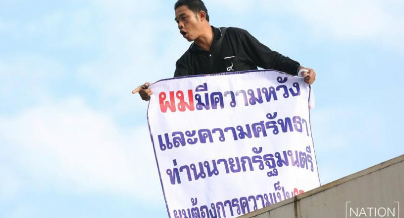 Chalerm Sonnothee 44, from Nan, carries a sign saying he has hope and faith in the prime minister while protesting atop the post office's roof inside the Government House Tuesday morning.