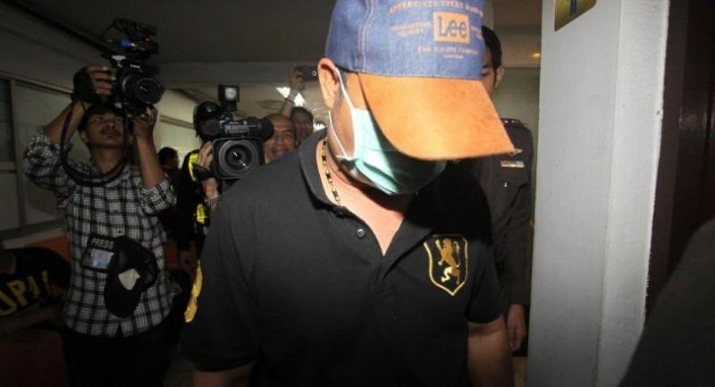 Pathumwanbased Thesakij officer Jiraphot Plaidoung (wearing cap and face mask) is taken for interrogation at Paholyothin Police Station in Bangkok after surrendering to police yesterday.  Photo Kittipon Maneerit