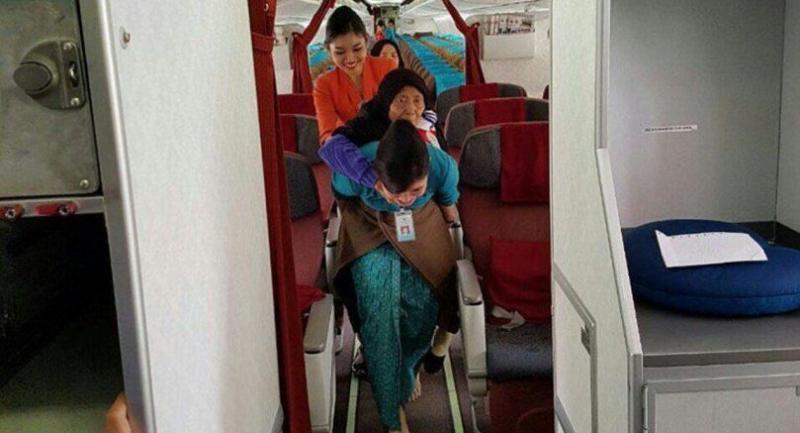 Vera carries an elderly passenger on her back after the GA-821 plane landed in Jakarta on Jan. 7.