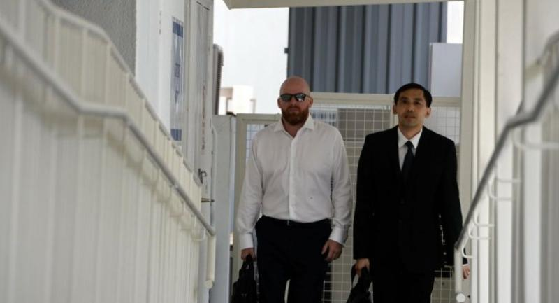 Swiss banker Jens Fred Sturzenegger (L) arrives with his lawyer Tan Hee Joek (R) at the state court in Singapore on Wednesday.  AFP PHOTO / ROSLAN RAHMAN