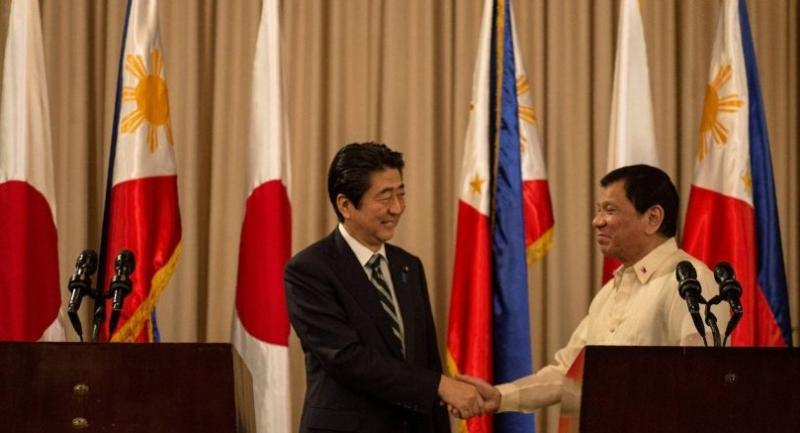 Philippine President Rodrigo Duterte (R) and Japanese Prime Minister Shinzo Abe (L) shake hands during a joint press statement at the Malacanang Palace in Manila on January 12, 2017./ AFP PHOTO