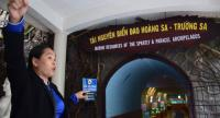 An official at the Institute of Oceanography shows an aquarium displaying species collected from the South China Sea. The institute renovated a transport tunnel made by France in the colonial era to create the aquarium, which is open to the public.