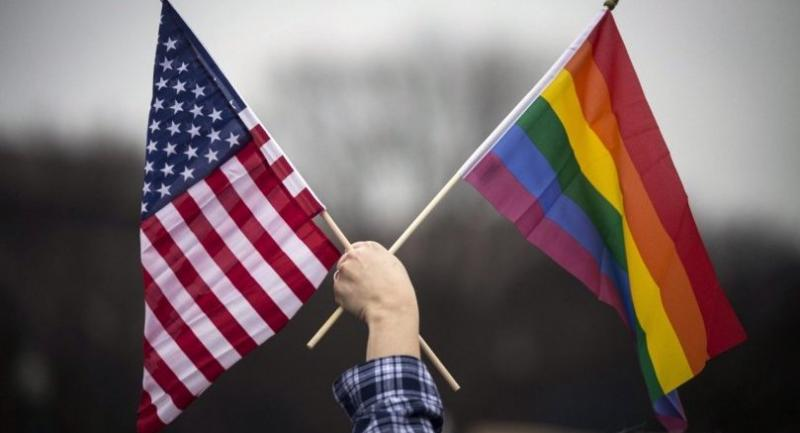 A participant holds both the US national flag (L) and the LGBT community's symbolic Rainbow flag (R) as people arrive on the mall for the Million Woman March in Washington, DC, USA, 21 January 2017. / EPA