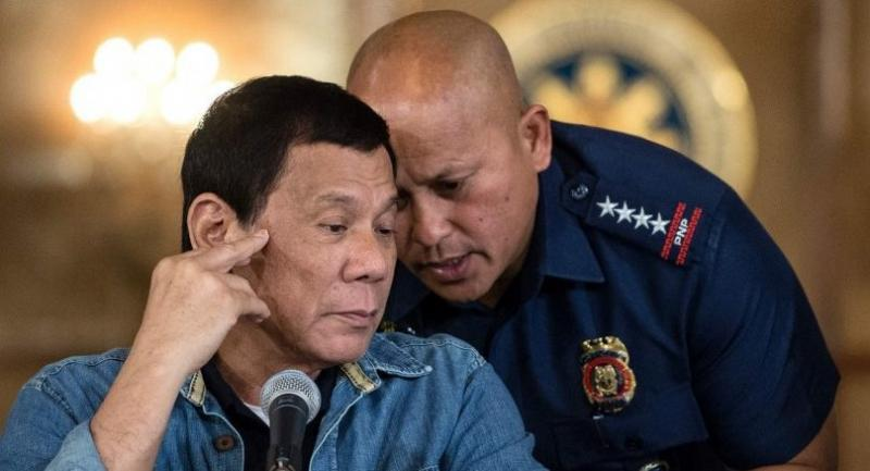 Philippine President Rodrigo Duterte (L) talks to Philippine National Police (PNP) Director General Ronald Dela Rosa (R) during a press conference at the Malacanang palace in Manila on January 30, 2017.  / AFP PHOTO