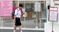 A pupil walks past the entrance of Chulalongkorn University