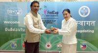Tamarine Tanasugarn is presented with the ITF Commitment Award by an ITF official Nitin Kannamwar.