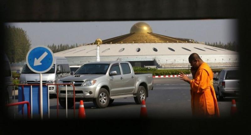 A monk talks on the phone near an entrance to the Dhammakaya Temple in Pathum Thani yesterday, when authorities conducted their third day of a search in the vast compound. This photo was taken through a grill gate.