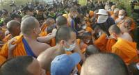 Dhammakaya Temple monks and followers clash briefly with police and Department of Special Investigation officials at the monastery in Pathum Thani yesterday.
