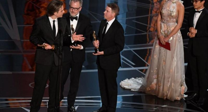 US Directors Byron Howard (L), Rich Moore (C) and producer Clark Spencer deliver a speech on stage after they won the award for Best Animated Feature Film for