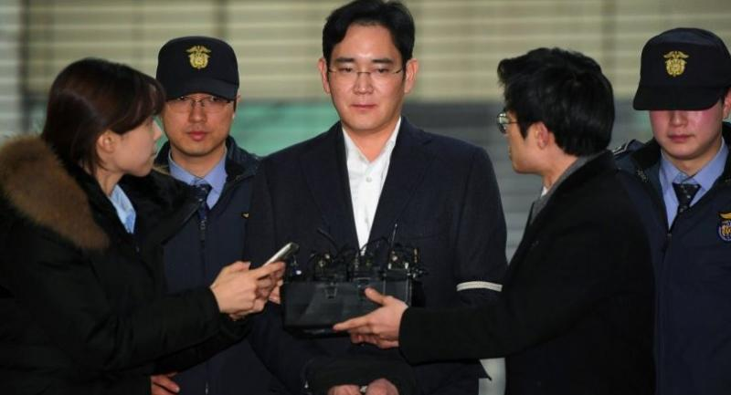 In a file photo taken on February 22, 2017 Lee Jae-Yong (C), vice chairman of Samsung Electronics, arrives for questioning at the office of a special prosecutor investigating a corruption scandal in Seoul. / AFP PHOTO / JUNG YEON-JE
