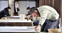 Yoan Rosenziveig repapers a shoji paper screen used at Nishihonganji temple in Shimogyo Ward, Kyoto.  Photo/The Yomiuri Shimbun