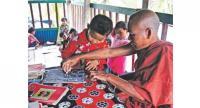 Buddhist monk Utuchitta Mohathero from Amkholapara temple in Patuakhali's Kuakata helps a boy write Rakhine alphabets. He takes free classes on Rakhine language at his