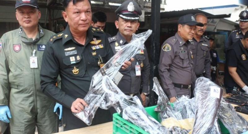 The officials display weapons seized from fugitive red-shirt leader's house