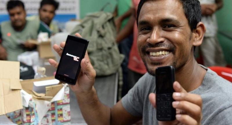 This photograph taken onTuesday shows a migrant worker with his new 3G phone (L) against an old 2G phone (R) that he was previously using, at a restaurant in Singapore. //AFP