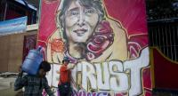 This file photo taken on November 13, 2015 shows a woman posing next to a graffiti depiction of Myanmar's opposition leader Aung San Suu Kyi outside the headquarters of the National League for Democracy party (NLD) in Yangon.//AFP