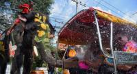 Foreign revellers on a tuk-tuk are sprayed with water by elephants during a preview yesterday of Songkran, the traditional Thai New Year water festival, at the historic World Heritage park in Ayutthaya.