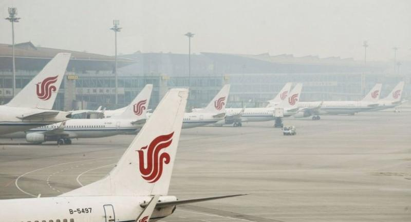 Air China planes are parked at Beijing Capital International Airport on April 6, 2017. / AFP PHOTO