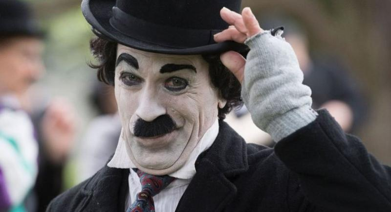 A man dresses as 'The Tramp' poses for a photo as people gather to mark the first anniversary of Chaplin