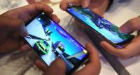 South Korean students play mobile games on Samsung Galaxy S8 smartphones at the company's showroom in Seoul on April 27, 2017. / AFP
