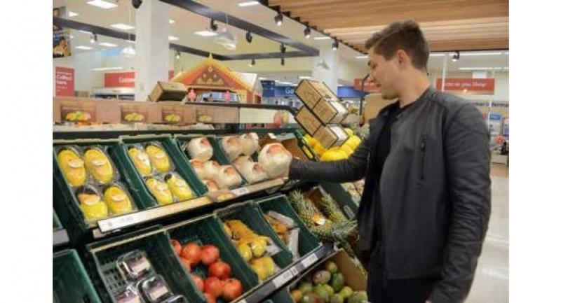 A shopper selects a coconut imported from Thailand at a Tesco store in the UK.