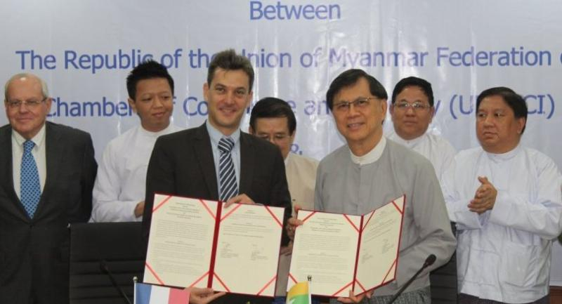 Julien Esch, president of CCI French Myanmar, and Maung Maung Lay, vice president of UMFCCI, show the memorandum of understanding.