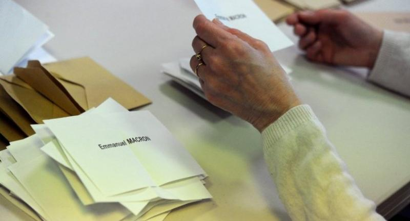 A polling official counts the ballots on May 7, 2017 in Quimper, western of France during the second round of French presidential election. / AFP