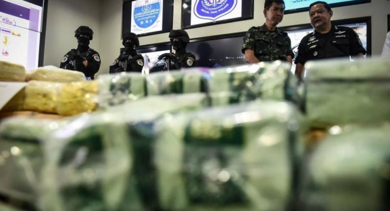 This photo taken on May 2, 2017 shows Thai law enforcement standing behind packages of