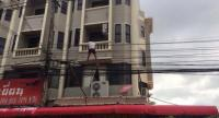 The man was walking on electric wires outside the fourth floor of a building in Phuket Town. Photo: Kritsada Mueanhawong