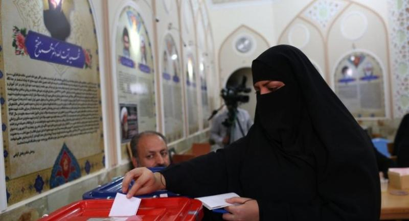 An Iranian woman casts her vote for municipal and presidential elections in the holy city of Qom, 130kms south of Tehran, on May 19, 2017. / AFP