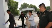 Ban Mai TAO's assistant chief Montha Charoensuksuwan is accompanied by police to the Criminal Court for Corruption and Misconduct Cases yesterday.