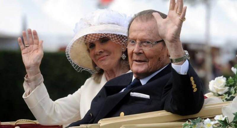 A file picture dated 25 June 2013 shows British actor Sir Roger Moore (R) and his Danish wife Kristina Tholstrup arriving in a horse-drawn carriage for the opening of the international horse show CHIO in Aachen, Germany.  EPA