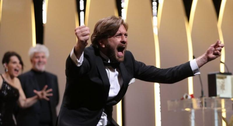 Swedish director Ruben Ostlund asks the audience to roar after he was awarded with the Palme d'Or for the film 'The Square' on May 28, 2017 during the closing ceremony of the 70th edition of the Cannes Film Festival in Cannes, southern France. / AFP