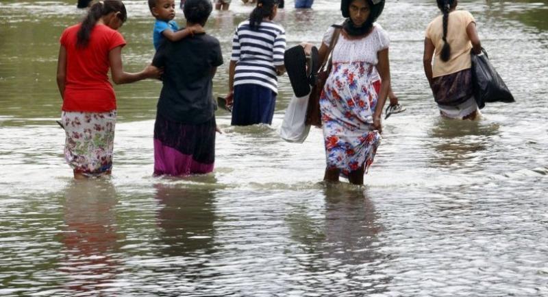 People walk in a flooded street in Bulathsinhala, some 79 kilometers from Colombo, Sri Lanka, 30 May 2017. /EPA