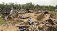 A Bangladeshi villager sits amid the desbris of a house destroyed by Cyclone Mora in Cox's Bazar on May 31, 2017. // AFP PHOTO