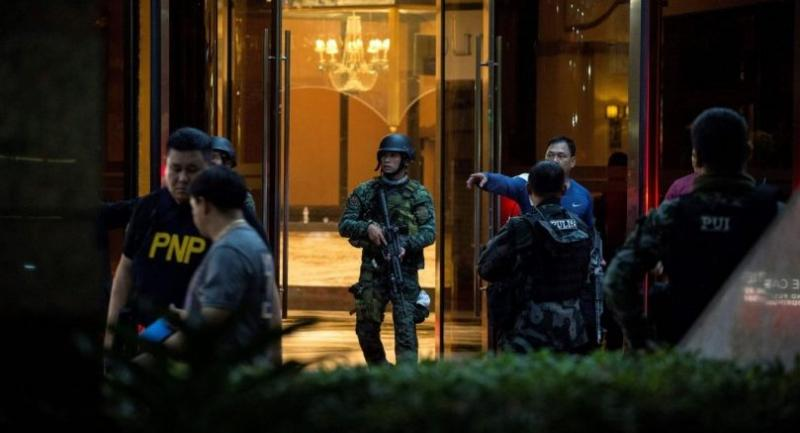 Philippines' police officers come out from the Resorts World Hotel in Manila on June 2, 2017 following an assault. /AFP