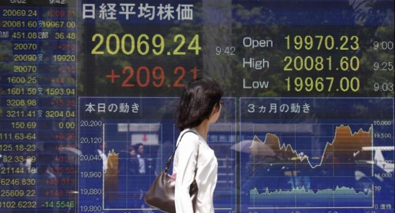 A woman looks at a stock quotation board flashing the key Nikkei index of the Tokyo Stock Exchange in front of a securities company in Tokyo on June 2, 2017. // AFP PHOTO